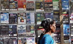 Woman walks past pirated DVDs and software on sale in Mumbai