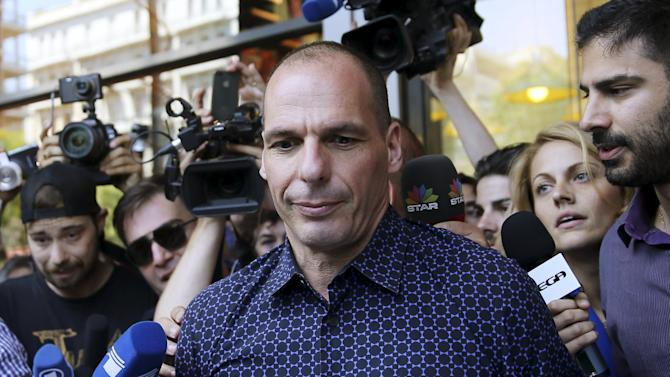 Former Greek Finance Minister Varoufakis is surrounded by the media as he leaves the Finance Ministry in Athens