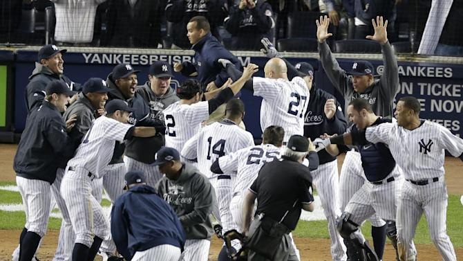 New York Yankees' Raul Ibanez (27) is mobbed by teammates at home plate after he hit the game-winning home run in the 12th inning in Game 3 of the American League division baseball series against the Baltimore Orioles on Wednesday, Oct. 10, 2012, in New York. The Yankees won 3-2. (AP Photo/Peter Morgan)