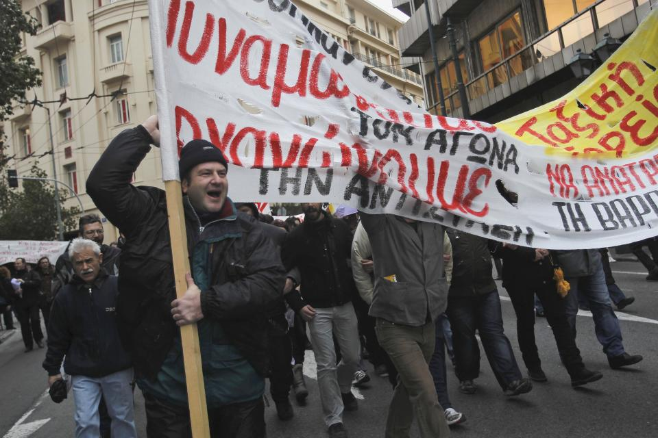 Protesters chant slogans as they carry a banner during a 24-hour strike on Tuesday, Feb. 7, 2012. A general strike against the impending cutbacks  stopped train and ferry services nationwide, while many schools and banks were closed and state hospitals worked on skeleton staff. (AP Photo/Petros Giannakouris)