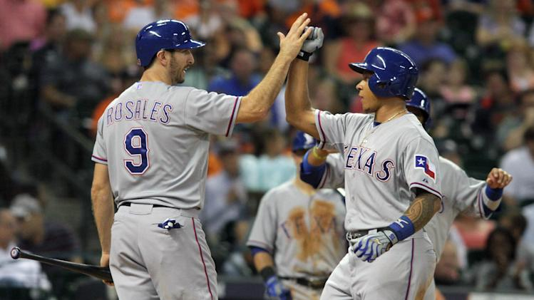 Texas Ranger Michael Choice, right, is greeted at home by Adam Rosales after his home run against the Houston Astros that scored Rosales and Tomas Telis in the fourth inning of a baseball game Friday, Aug. 29, 2014, in Houston. (AP Photo/Richard Carson)