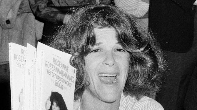 """FILE - In this Sept. 27, 1983 file photo, actress and comedienne Gilda Radner holds up copies of her book, """"Roseanne Roseannadanna's  """"Hey, Get Back To Work,"""" at a New York bookstore. The Madison, Wis.-area chapter of Gilda's Club  is the latest to change its name to the Cancer Support Community, a move its director said was necessary because young people don't know who Radner was.  (AP Photo/Suzanne Vlamis)"""
