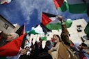 Palestinians wave flags during a rally in support of President Abbas' efforts to secure a diplomatic upgrade at the United Nations, in Ramallah
