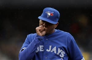 Toronto Blue Jays pitcher Esmil Rogers blows on his hand in the fifth inning of a baseball game against the Detroit Tigers in Detroit, Thursday April 11, 2013. (AP Photo/Paul Sancya)