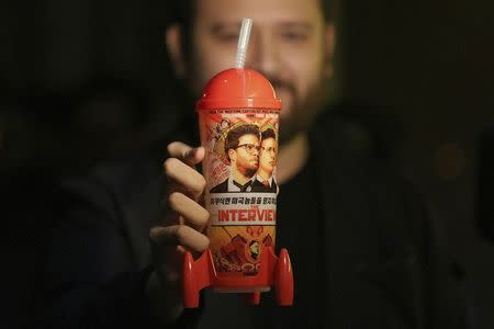 "Man holds a ""The Interview"" souvenir cup before a midnight screening of ""The Interview"" in Los Angeles, California"