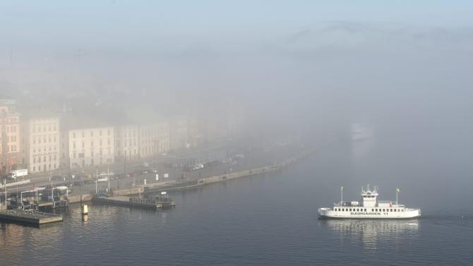 A ferry heads through fog into central Stockholm Old Town harbour