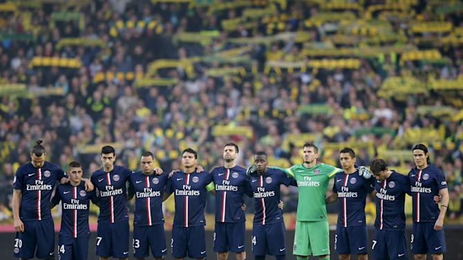 Paris St Germain players stand during a minute of silence held for the victims of the earthquake that shook Nepal, before their French Ligue 1 soccer match against FC Nantes at the Beaujoire stadium in Nantes