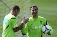 "Portugal's defender Pepe (L) jokes with forward Cristiano Ronaldo during a training session on May 22. Portugal cannot afford to rely too heavily on their talismanic captain Ronaldo at Euro 2012 because he ""can't do everything on his own"", warned centre-back Pepe on Thursday"