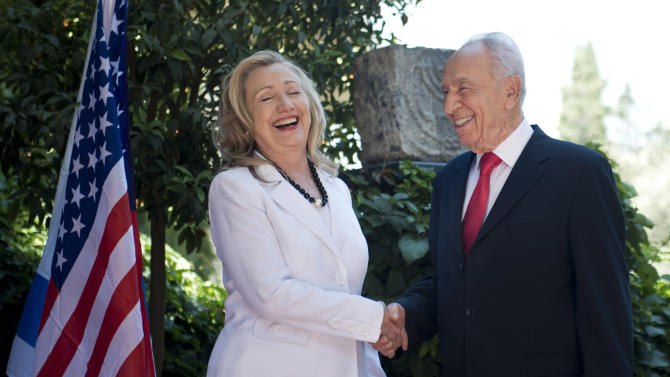 Israel's President Shimon Peres, right, and U.S. Secretary of State Hillary Rodham Clinton, left, laugh as they shake hands before their meeting at the President's residence in Jerusalem, Monday, July 16, 2012. Although Clinton's agenda is designed to cover the breadth of U.S.-Israeli relations, the lack of action on peace talks between Israel and the Palestinians will be in the spotlight. (AP Photo/ Brendan Smialowski, Pool)