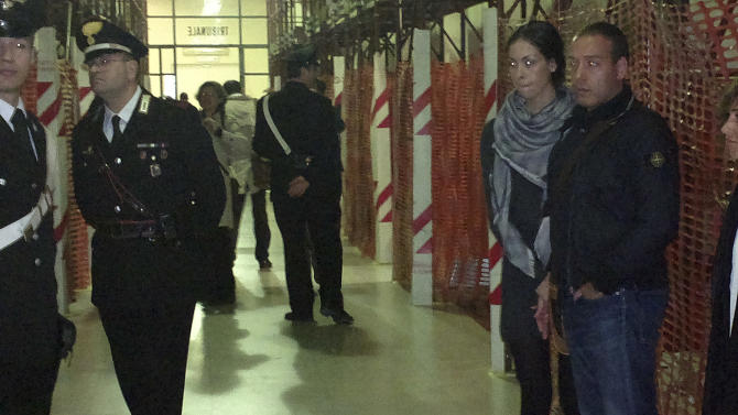 Karima el-Mahroug, from Morocco, the woman at the center of a sex scandal involving former Italian Premier Silvio Berlusconi, is seen standing at right with her husband Luca Risso as she waits to be called to testify for the first time in the trial of three Berlusconi aides charged with recruiting her and other women for prostitution, in Milan's courthouse, Italy, Friday, May 17, 2013. El-Mahroug, known by the nickname Ruby Heart Stealer, has made carefully orchestrated statements to the media since the scandal broke but has never publicly given sworn testimony. Both she and Berlusconi deny having had sex. Prosecutors in Berlusconi's separate trial on charges of paying for sex with a minor and trying to cover it up say her testimony is unreliable and are relying on her sworn statements. (AP Photo/Luca Bruno)