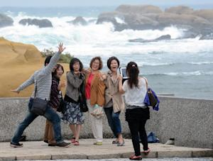 Tourists pose for pictures at Hoping island, in Keelung, …