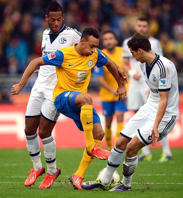 Braunschweig's Karim Bellarabi, center, and Schalke's Dennis Aogo , left, and Leon Goretzka, right, challenge for the ball during the German first division Bundesliga soccer match between Eintracht Br