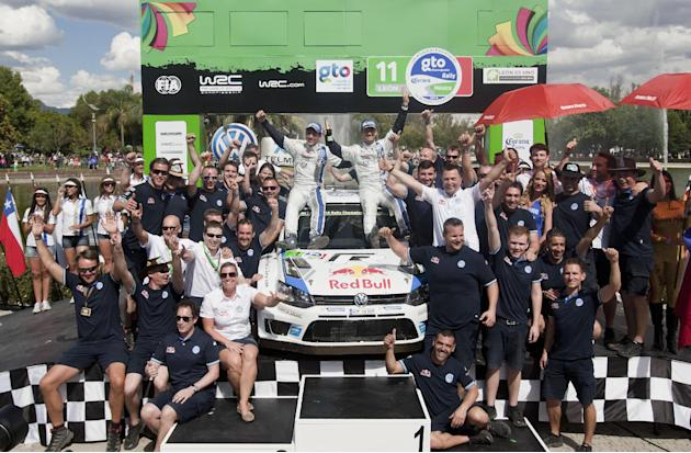 Volkswagen Motorsport team driver Sebastian Ogier, sitting on car right, and co-driver Julien Ingrassia, both from France, pose for photos with their team as they celebrate winning the Mexico Rally in