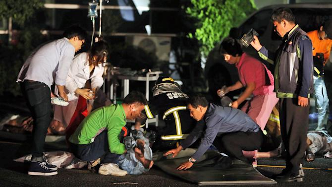Rescue workers treat victims of a major fire at a hospital in Jangseong, South Korea, Wednesday, May 28, 2014. South Korean officials said at least 20 patients and one nurse died in a fire at a hospital in the southwestern city of Jangseong. (AP Photo/Yonhap, Hyung Min-woo) KOREA OUT