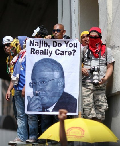 A protester is seen holding a picture of Malaysia's prime Minister Najib Razak