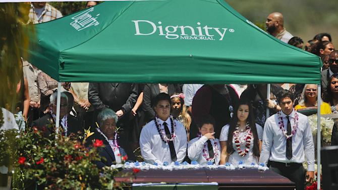 The casket of former football star Junior Seau, who committed suicide last week, rests in front of his children, mother and father, far left, Friday, May 11, 2012, at his burial in Oceanside, Calif. (AP Photo/Lenny Ignelzi)