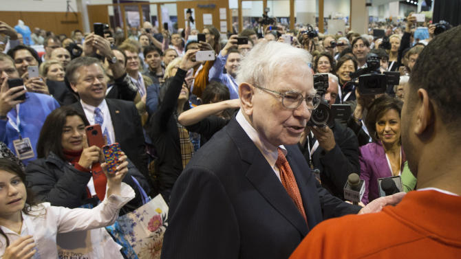 """Investor Warren Buffett is surrounded by hundreds of Berkshire Hathaway shareholders and journalist as he talks to Chris """"Handles"""" Franklin of the Harlem Globetrotters before the shareholders meeting in Omaha, Neb., Saturday, May 4, 2013. Tens of thousands attend Berkshire Hathaway shareholder meeting to hear Warren Buffett and Charlie Munger answer questions for more than six hours. No other annual meeting can rival Berkshire's, which is known for its size, the straight talk Buffett and Munger offer and the sales records shareholders set while buying Berkshire products. (AP Photo/Nati Harnik)"""