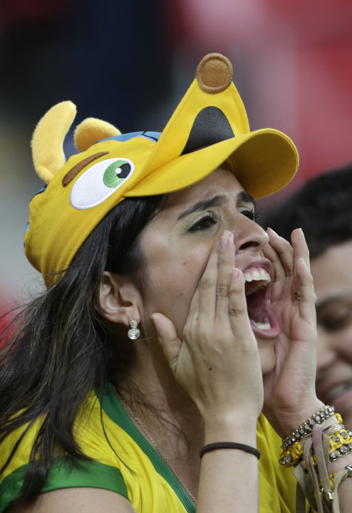 A fan wearing a cap featuring Fuleco, the 2014 World Cup mascot, shouts before the Confederations Cup Group A soccer match between Italy and Japan at the Arena Pernambuco in Recife