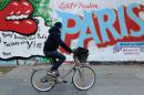 In this photo taken on Sunday Nov. 22, 2015, a man rides his bicycle by a painted wall, in Paris. As Paris reeled from the worst attacks France has known since the end of World War II, its street artists took to city walls and billboards to paint notes of defiance. (AP Photo/Binta Epelly)