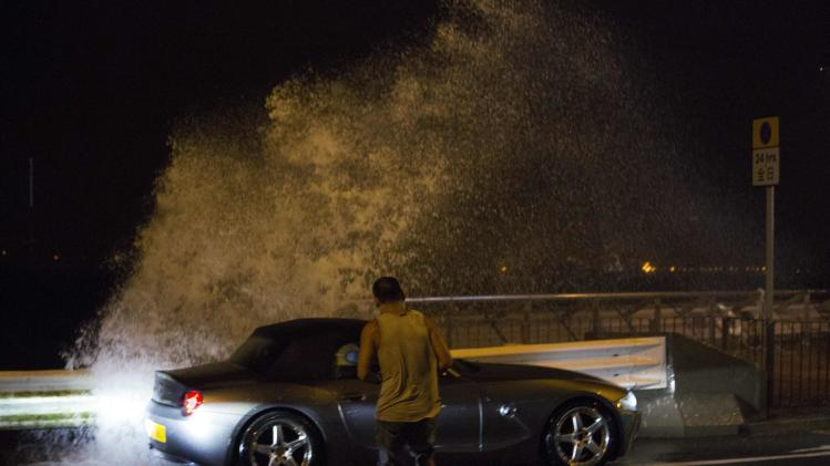 Man tries to get back into his car as a wave surges past a barrier on the shore during Typhoon Usagi in Hong Kong