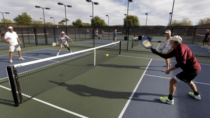 "In this Monday, Dec. 3, 2012 photo, clockwise from left; Gary Dyson, Del Teter, Donna Shattenberg and David Bone compete in a game of pickleball at Sun City West senior community in Surprise, Ariz. A hybrid of tennis, badminton and table tennis, pickleball is played on a court a quarter the size of a tennis court, with hard rackets and a variety of whiffle ball. ""It's really easy to learn, it's a lot of fun and it's a very social game because you're in a small area with a lot of interaction,"" said Bill Booth, president of the USA Pickleball Association.  (AP Photo/Matt York)"