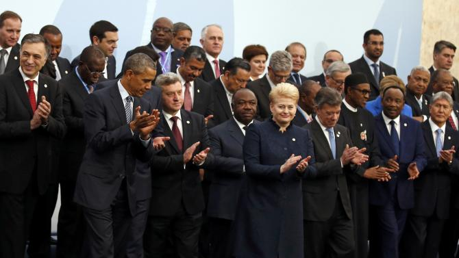 U.S President Obama applauds after a family photo with fellow world leaders during the opening day of the World Climate Change Conference 2015 (COP21) at Le Bourget