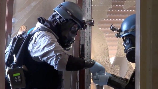 In this image taken from video obtained from the Shaam News Network Thursday, Aug. 29, 2013, which has been authenticated based on its contents and other AP reporting, members of the UN investigation team take samples from the ground in the Damascus countryside of Zamalka, Syria. United Nations experts are investigating the alleged use of chemical weapons in Syria as the United States and its allies prepare for the possibility of a punitive strike against President Bashar Assad's regime, blamed by the Syrian opposition for the attack. The international aid group Doctors Without Borders says at least 355 people were killed in the Aug. 21 attack in a suburb of Damascus, the Syrian capital. (AP Photo/Shaam News Network via AP video)