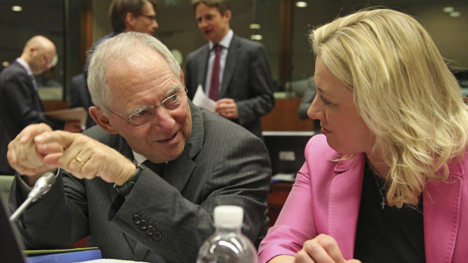 German Finance Minister Wolfgang Schaeuble, left, talks with Finnish Finance Minister Jutta Urpilainen, during the EU finance ministers meeting, at the European Council building in Brussels, Tuesday, May 14, 2013. European Union finance ministers seek ways to cut down on tax evasion, action British Chancellor George Osborne says is particularly important in current circumstances. (AP Photo/Yves Logghe)