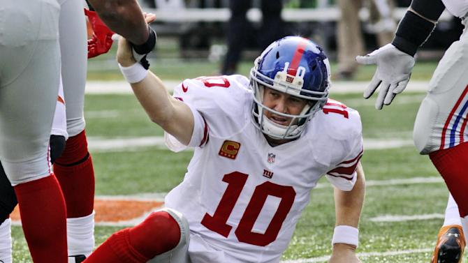 New York Giants quarterback Eli Manning is helped up after being sacked in the second half of an NFL football game against the Cincinnati Bengals, Sunday, Nov. 11, 2012, in Cincinnati. (AP Photo/Tom Uhlman)