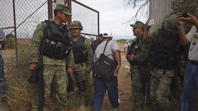 A vigilante walks between soldiers to voluntarily cooperate in a shootout investigation in La Ruana, Michoacan