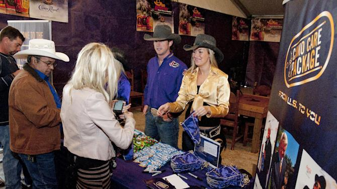 Rodeo fans pack Crown Royal CAMO Care Packages to be sent to active-duty troops overseas, Saturday, Feb. 9, 2013, at the San Antonio Stock Show and Rodeo in San Antonio. (Darren Abate/AP Images for Crown Royal)