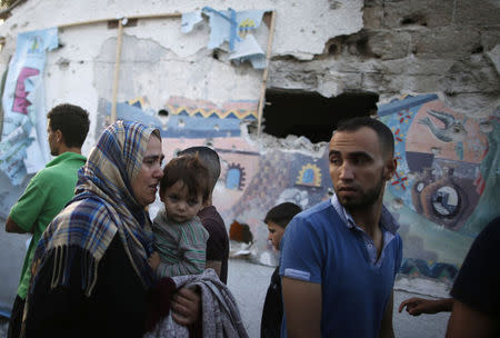 A Palestinian woman cries as she holds her son at a United Nations-run school sheltering Palestinians displaced by an Israeli ground offensive, in Jebalya refugee camp in the Gaza Strip