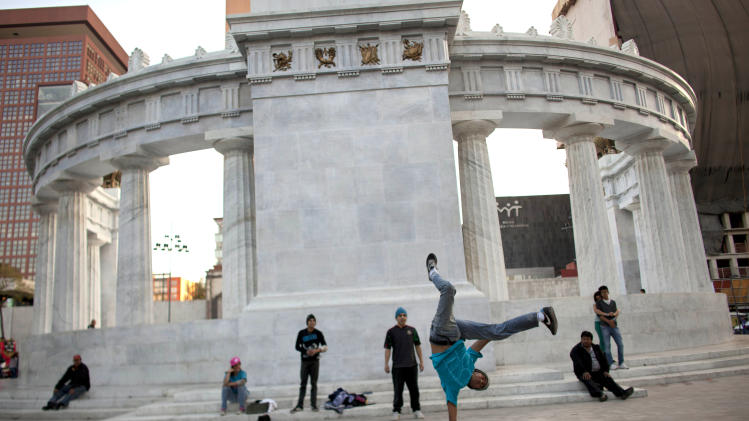 """A dancer shows off his moves at the Alameda Central in Mexico City, Wednesday, Dec. 27, 2012.  Made iconic in the Diego Rivera mural """"Dream of a Sunday Afternoon in the Alameda,"""" city officials have cleared the swarms of vendors and remodeled the historic plaza. Mexico City's government is trying to transform one of the world's largest cities by beautifying public spaces, parks and monuments buried beneath a sea of honking cars, street hawkers, billboards and grime following decades of dizzying urban growth. (AP Photo/Alexandre Meneghini)"""