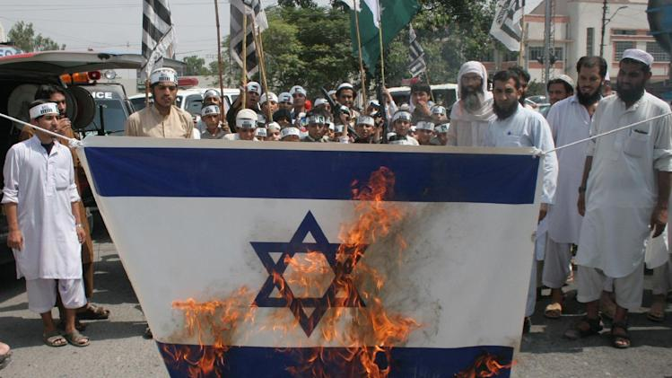 Pakistani protesters burn a representation of an Israeli flag during a protest against the Israeli bombings in the Gaza strip, in Peshawar, Pakistan, Tuesday, July 22, 2014. Overnight, the Israeli military said it bombed more than 180 militant targets in Gaza, including concealed rocket launchers, a weapon manufacturing facility and surface-to-surface missile launchers. Gaza police spokesman Ayman Batniji said mosques, a sports complex and the home of a former Hamas military chief were hit. (AP Photo/Mohammad Sajjad)