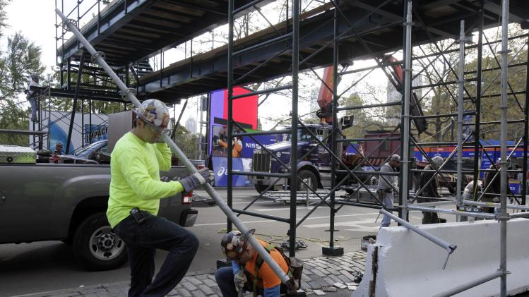 Workers assemble the photo bridge at the finish of the New York City Marathon in New York's Central Park, Friday, Nov. 2, 2012. Under growing pressure as thousands still shivered from Sandy, the narathon was canceled Friday by Mayor Michael Bloomberg after mounting criticism that this was not the time for a race. (AP Photo/Richard Drew)
