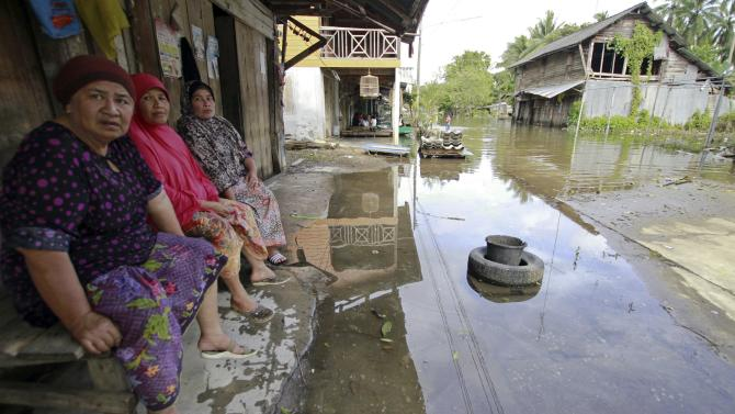 Women sit outside a home in a flooded area in Yala province