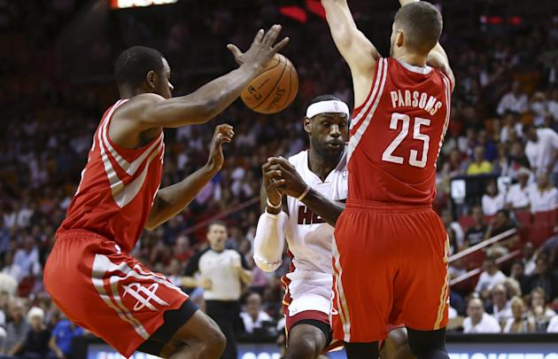 As Houston Rockets players Terrence Jones (6) and Chandler Parson (25) apply pressure, they force Miami Heat's LeBron James to loose control of the ball during the first half of an NBA  basketball