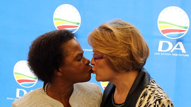 South African anti-apartheid activist Mamphela Ramphele, left, greets Helen Zille, right, the head of the South African Democratic Alliance political party during a press conference in Cape Town, South Africa, Tuesday, Jan. 28, 2014. The former anti-apartheid activist who was close to Steve Biko and was a World Bank executive merged her party Tuesday with South Africa's main opposition party, the Democratic Alliance, and will be its presidential candidate, challenging the ruling African National Congress whose popularity has eroded amid corruption scandals and other problems. (AP Photo/ Nardus Engelbrecht)