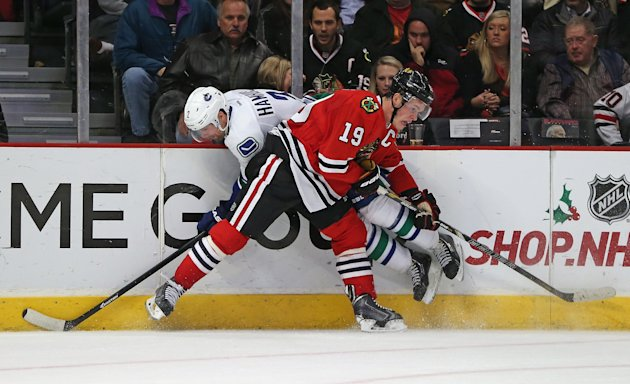 CHICAGO, IL - DECEMBER 20: Jonathan Toews #19 of the Chicago Blackhawks collides with Dan Hamhuis #2 of the Vancouver Canucks at the United Center on December 20, 2013 in Chicago, Illinois. The Canucks defeated the Blackhawks 3-2 in a shootout. (Photo by Jonathan Daniel/Getty Images)