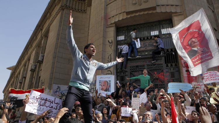 "Egyptian protesters chant slogans against Islamist President Mohammed Morsi slogans during a protest in front of the prosecutor general's office in Cairo, Egypt, Friday, March 29, 2013. Hundreds of activists demonstrated to show solidarity with political activists charged by the prosecutor general with inciting violence during last week's clashes near the Muslim Brotherhood's Cairo headquarters. Arabic banner at left reads, ""none can threaten us,"" and at center, ""freedom for activist Hassan Mustafa.""(AP Photo/Amr Nabil)"