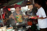 Soon Chuan Choo (C) passing char kway teow to a customer in Georgetown, the state of Penang&#39;s capital city.