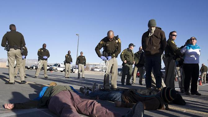 """Protesters are arrested after staging a """"die-in"""" during an anti-drone protest at Creech Air Force Base, 50 miles northwest of Las Vegas, Friday, March 6, 2015. Officials said more than a hundred people assembled outside the base in Indian Springs. Advocacy groups  have been protesting for a week against remotely piloted aircraft flying armed missions in Afghanistan, Pakistan, Yemen and Somalia. (AP Photo/Las Vegas Sun, Steve Marcus) LAS VEGAS REVIEW-JOURNAL OUT"""