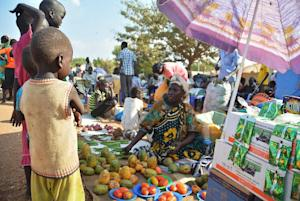 A displaced woman sells fruit at a crowded IDP  encampment …