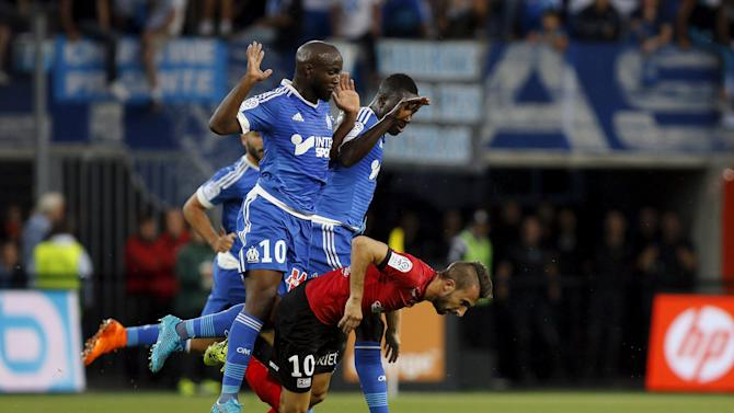 Olympique Marseille's Diarra and Mendy challenges Guingamp's Benezet during their French Ligue 1 soccer match at the Roudourou stadium in Guingamp