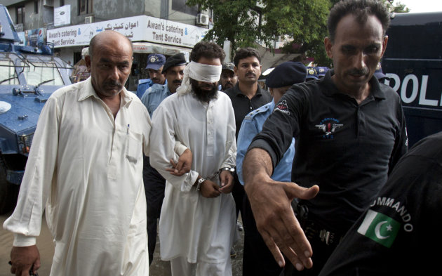 Pakistani police officers escort blindfolded Muslim cleric Khalid Chishti to court in Islamabad, Pakistan, Sunday, Sept. 2, 2012. In the latest twist in a religiously charged case that has focused att