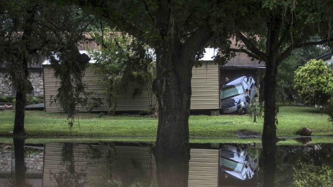 Flood damaged vehicles and debris are strewn across lawns throughout the length of Bogie Drive in San Marcos, Texas