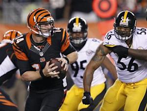 Cincinnati Bengals quarterback Dalton throws under pressure from the Pittsburgh Steelers' Woodley and Jones during their NFL football game at Paul Brown Stadium in Cincinnati