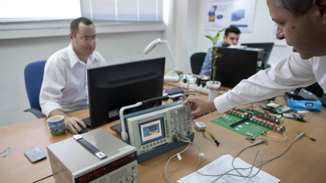 In this photograph made on Thursday Nov. 28, 2013 employees work at CellBuddy office in Tel Aviv, Israel. For international travelers tired of paying steep roaming charges on their cellphones, an Israeli start-up says it has found a solution. Cell Buddy says its app can turn any smartphone into a local handset, allowing travelers to choose from an array of calling and data plans with carriers in dozens of countries. (AP Photo/Dan Balilty)