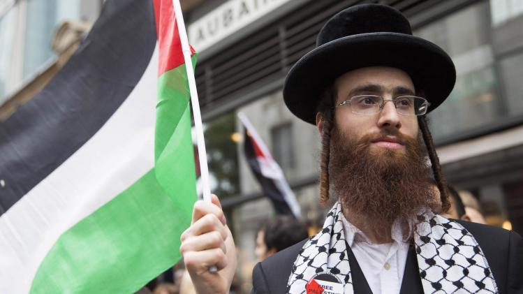 An ultra-Orthodox Jew holds a Palestinian flag during a protest against Israel's air strikes in Gaza in London