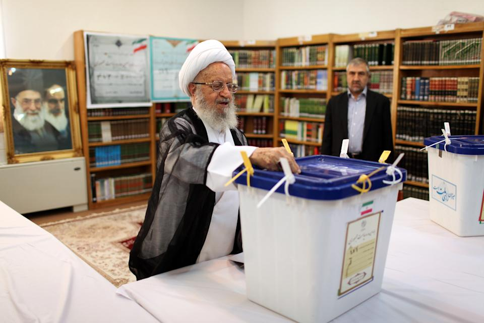 Grand Ayatollah Nasser Makarem Shirazi casts his ballot during presidential elections at a polling station in Qom, 125 kilometers (78 miles) south of the capital Tehran, Iran, Friday, June 14, 2013. (AP Photo/Ebrahim Noroozi)